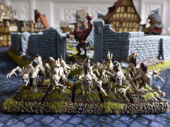 Two ranks of ten ghouls with a walled cemetery in the background