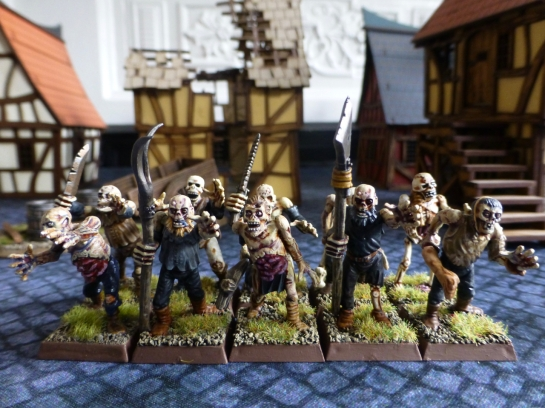 Two ranks of zombies with crude weapons and pitchforks