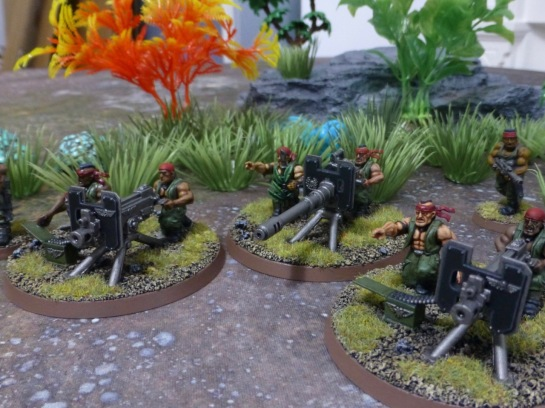 Three heavy weapon teams lined up in the jungle