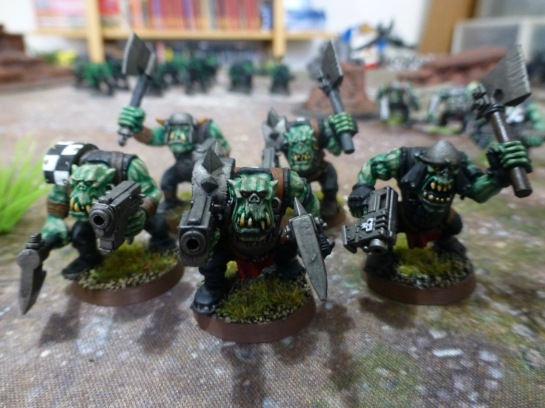 Five Orks with pistols and axes storming forward
