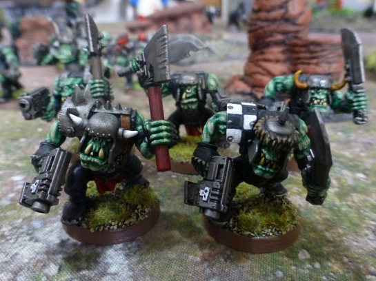 Head on view of five Orks with pistols, axes and crude swords