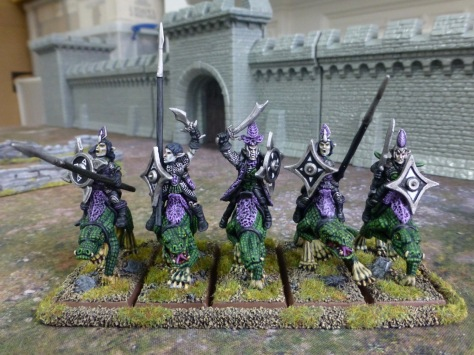 Five Dark Elves riding giant lizards in front of a castle