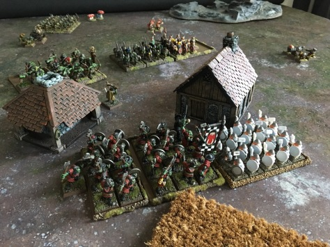 Battle scene with a mix of painted and unpainted miniatures