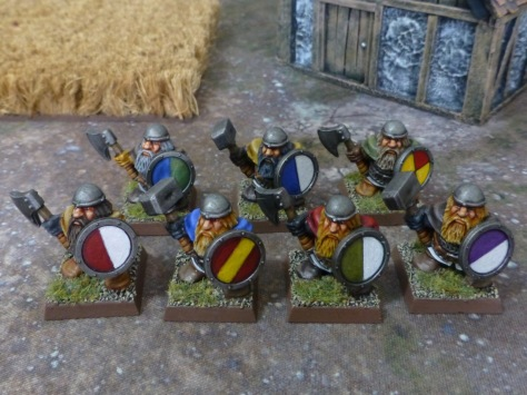Look from above on dwarf warriors carrying colourful round shields
