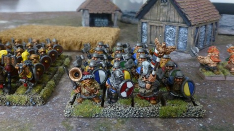 Regiment of dwarf warriors between other units outside of a small settlement
