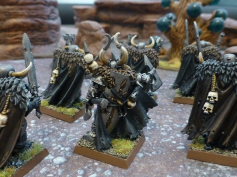 Back view of several warriors in heavy cloaks and furs