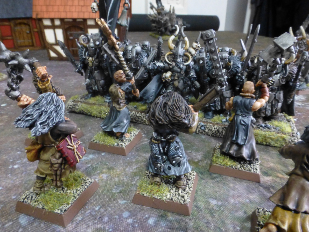 Back view of flagellants rushing a line of heavily armoured dark warriors