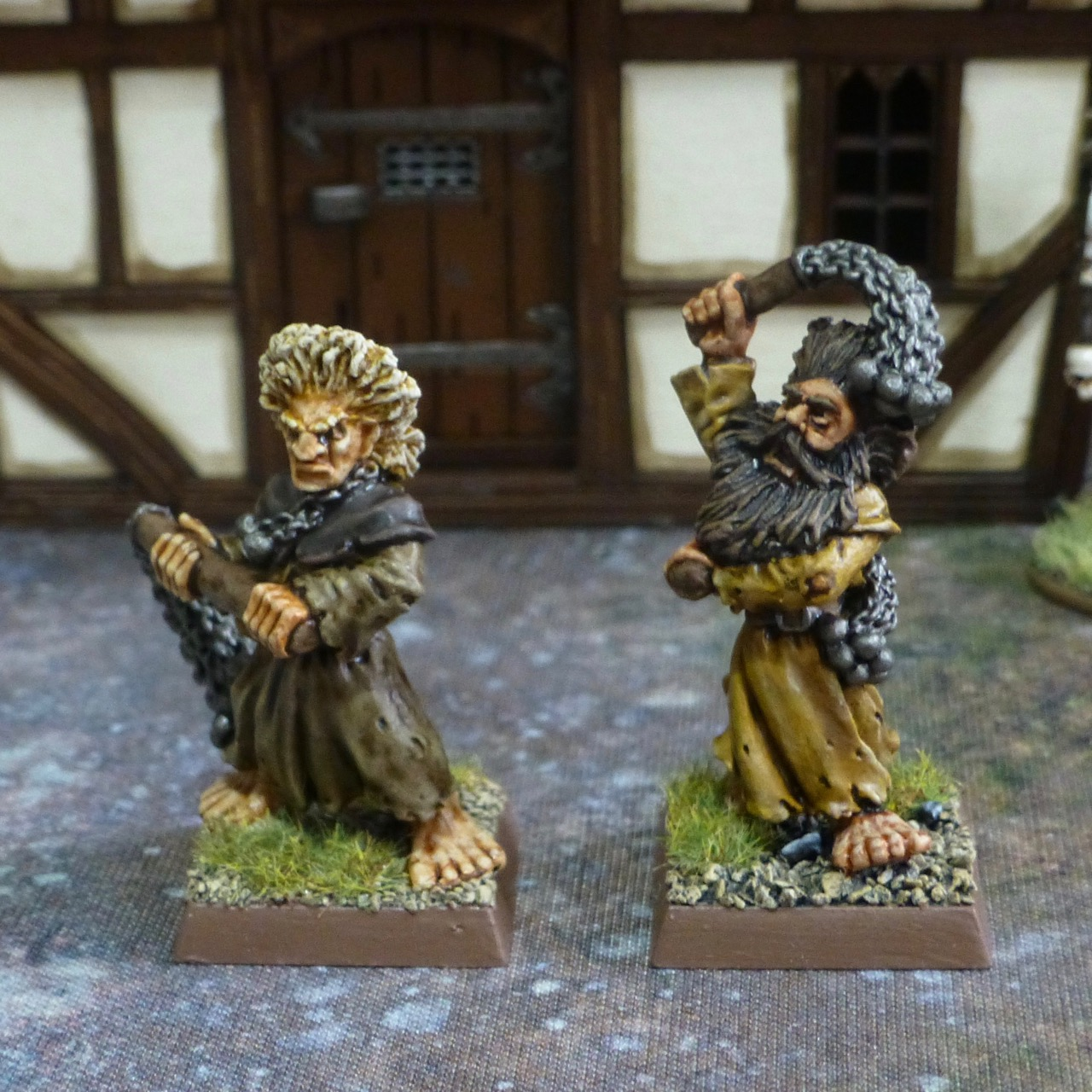Two flagellants with manes of hair and a range of flails