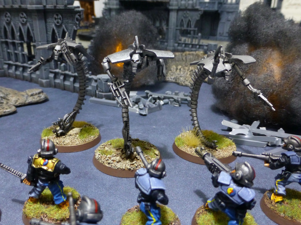 Three ghostlike silver robots rushing a squad of human soldiers