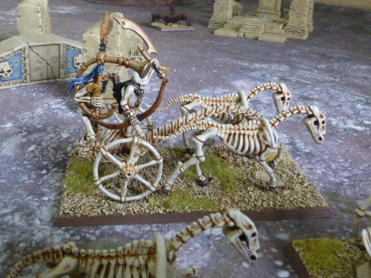 Side view of a skeleton chariot carrying a warrior with a large bronze horn instrument