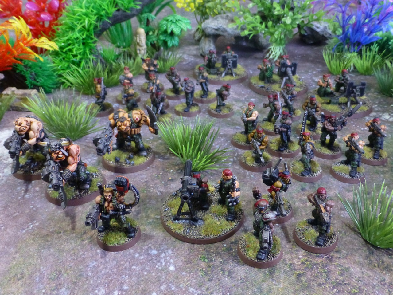 Multiple squads of soldiers in green fatigues among jungle plants