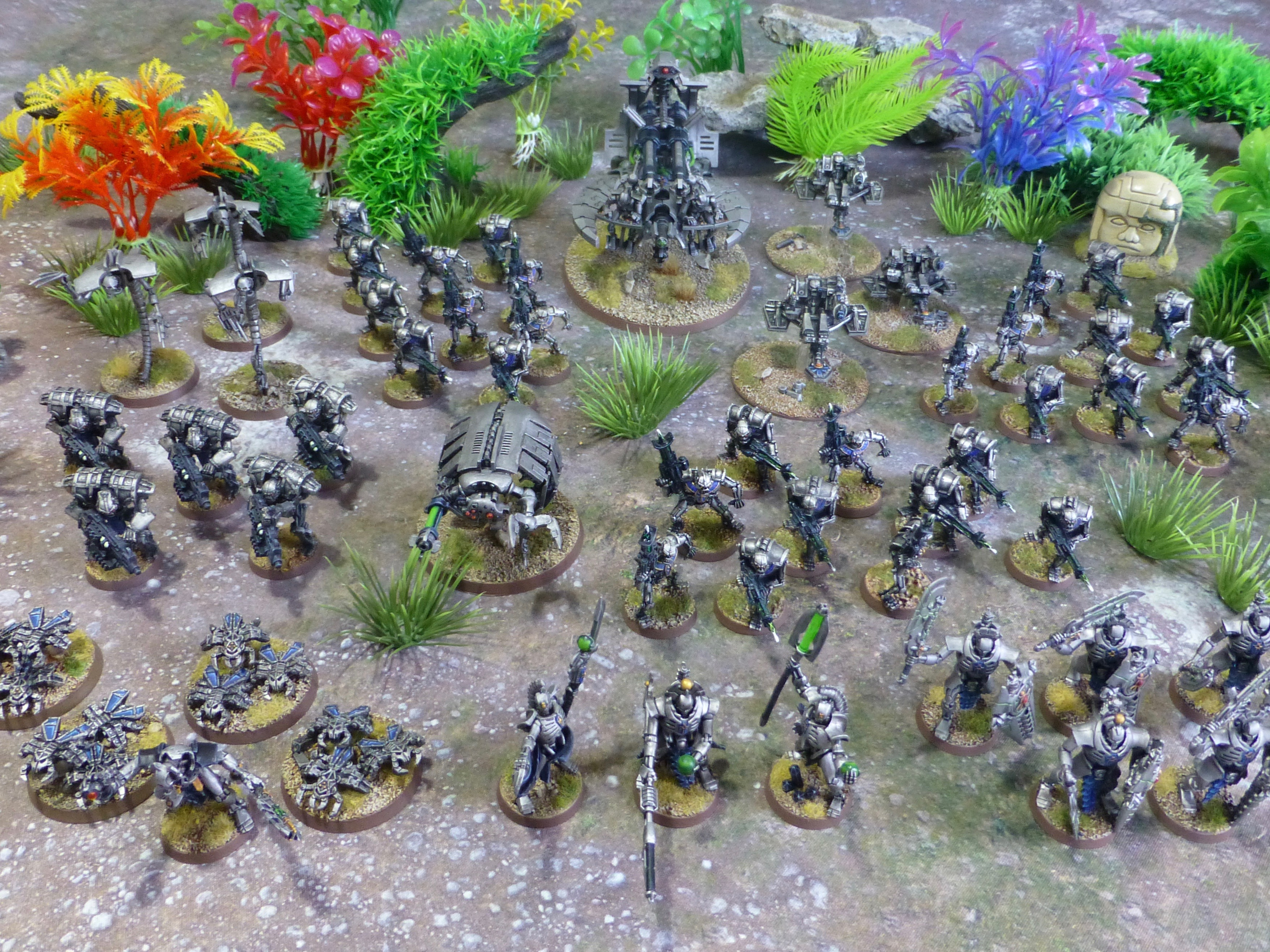 View from above on a force of dozens of robotic metal warriors and war machines in jungle terrain