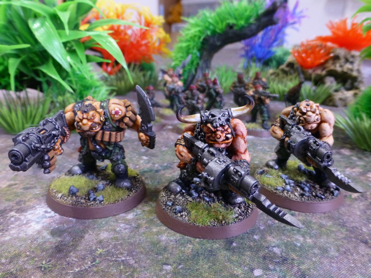 Three Ogryns in a jungle of vibrant plants