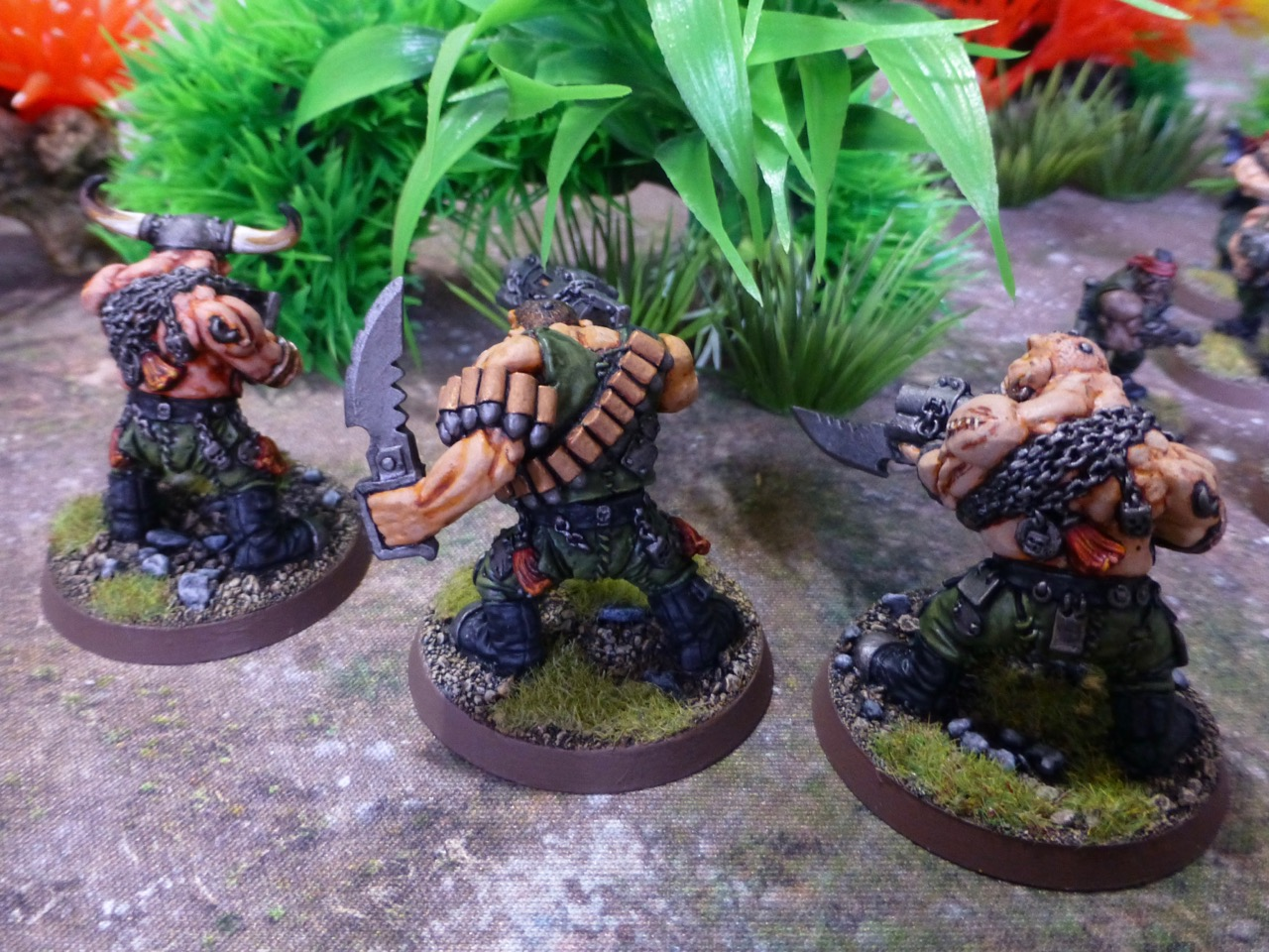 Back view of three Ogryns in front of green foliage